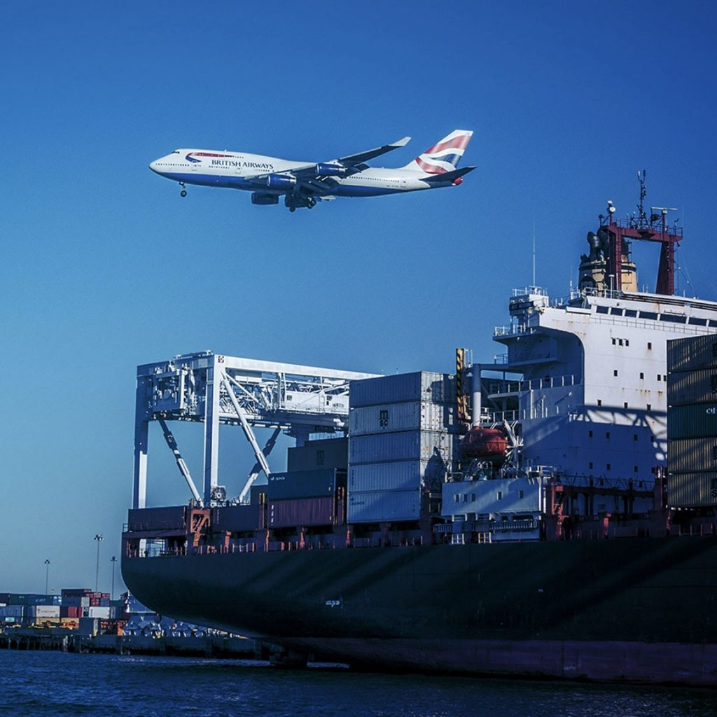Plane flying over container ship